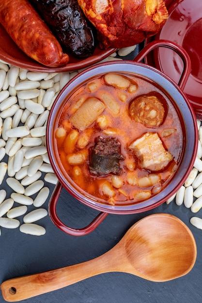 Аппетитная ложка блюдо. восхитительно для осени, зимы и всего года. астурийская фабада, типичное блюдо астурии (испания). рагу из бобов (белая фасоль) с чоризо, беконом, черным пудингом, беконом,… Premium Фотографии