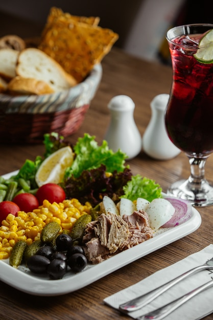 Appitizers plate with olive, corn, boiled beef, lettuce, cornichon, tomato, lemon Free Photo