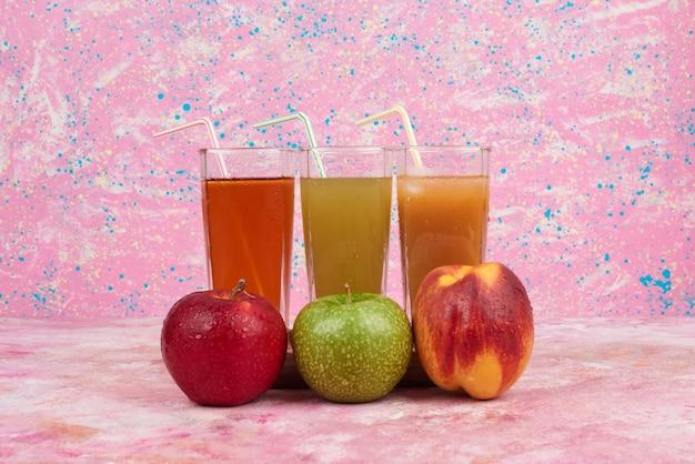 カラフルなグラスジュースとリンゴと桃。 無料写真