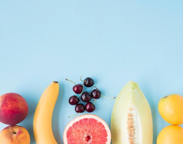 Apple; banana; cherries; grapefruit; muskmelon and lemons on blue background Free Photo