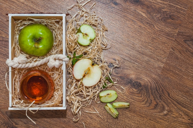 Apple cider vinegar with green apple in wooden crate on wooden table Free Photo