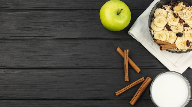 Apple and a cinnamon with a bowl of oatmeal with banana slices Free Photo