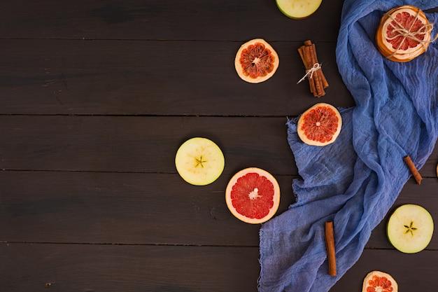 リンゴ、グレープフルーツ、シナモンの青い布 Premium写真