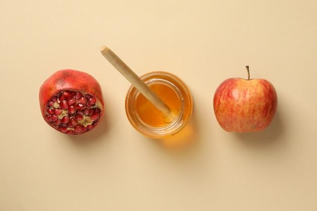 Яблоко, мед и гранат на бежевом, вид сверху. домашнее лечение Premium Фотографии