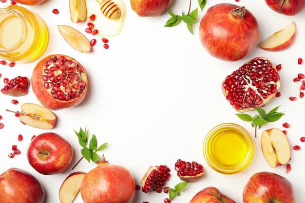 Яблоко, мед и гранат на белом, место для текста Premium Фотографии