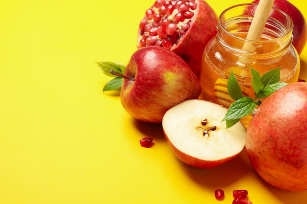 Яблоко, мед и гранат на желтом, место для текста Premium Фотографии