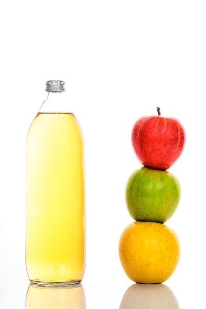 ガラス瓶に入ったリンゴジュースと3つの熟したリンゴ 無料写真