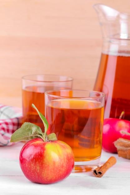 新鮮なリンゴとシナモン、自然な木製の背景にリンゴジュース Premium写真