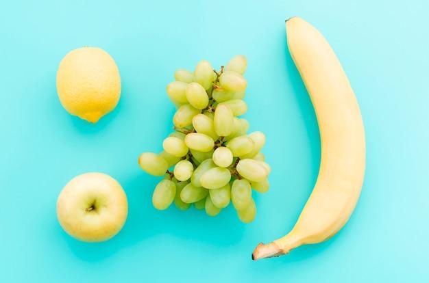 Apple lemon grapes and banana on turquoise surface Free Photo