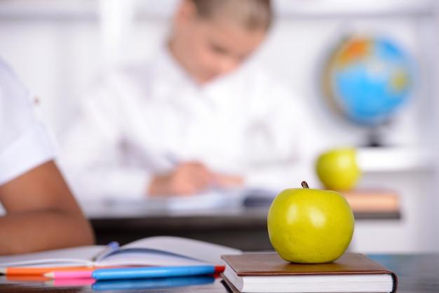 Apple lies on the book, school girl. Premium Photo