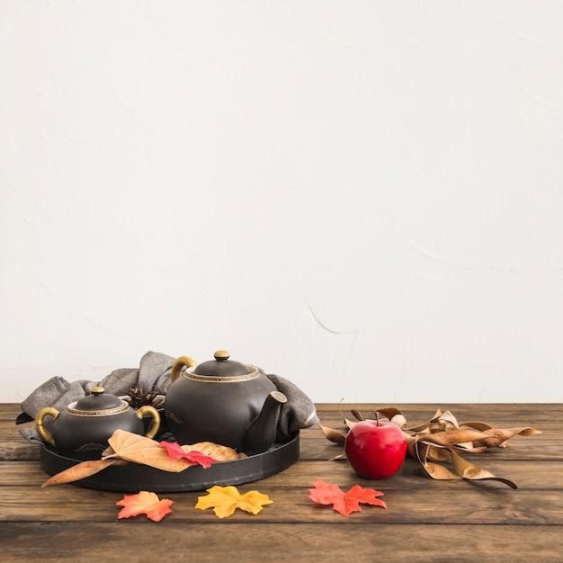 Apple near leaves and tea set Free Photo