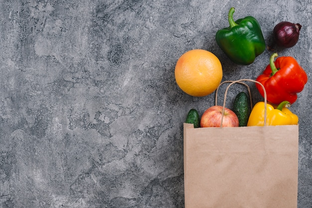 Apple; orange and vegetables spilled from paper bag on concrete backdrop Free Photo