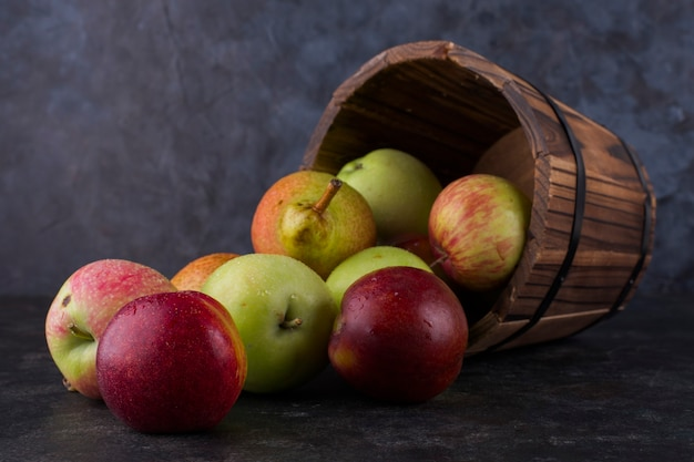 Apple, peach and pears out of a wooden bucket Free Photo