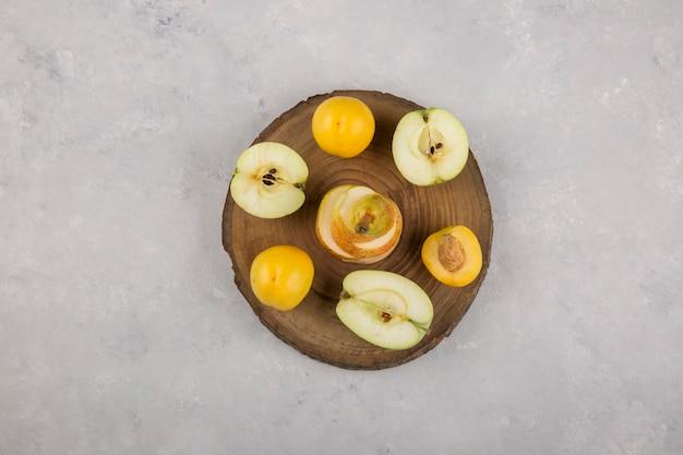 Яблоко, груша и персики на деревяшке посередине Бесплатные Фотографии