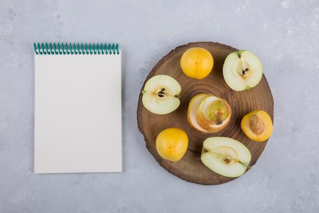 Яблоко, груша и персики на дереве, с записной книжкой в сторону Бесплатные Фотографии