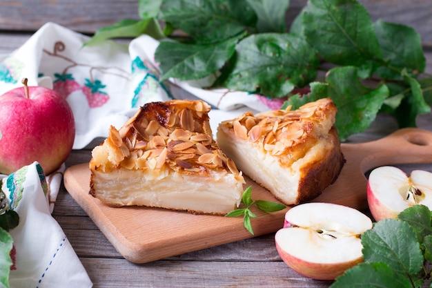 Яблочный пирог и красные яблоки на деревянном столе Premium Фотографии