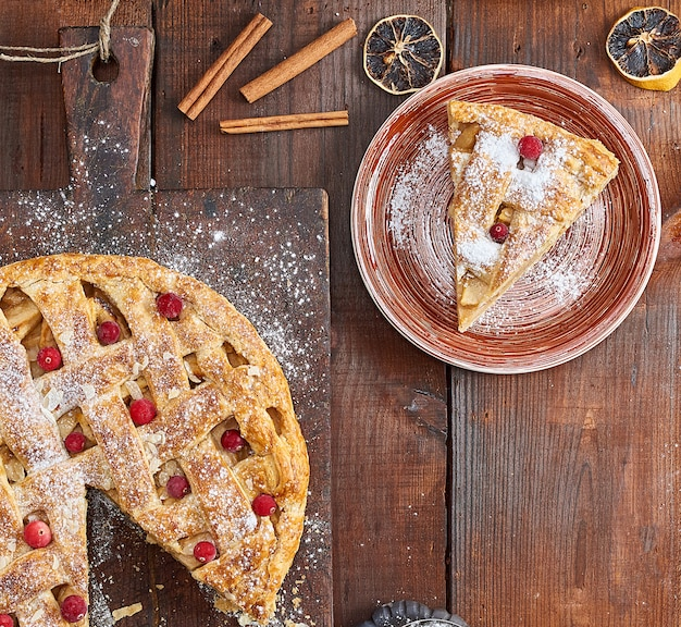Apple pie on a rectangular old brown cutting board sprinkled with powdered sugar Premium Photo