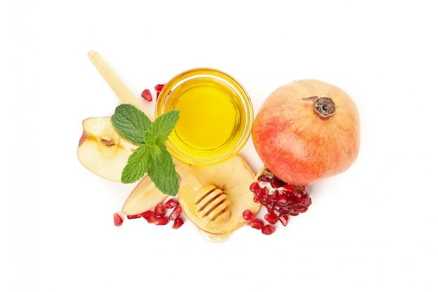 Яблоко, гранатовое дерево и мед изолированные на белизне. натуральное лечение Premium Фотографии