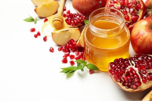 Яблоко, гранат и мед на белом, крупным планом. домашнее лечение Premium Фотографии