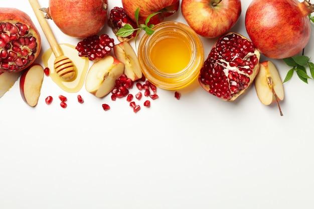 Яблоко, гранат и мед на белом, вид сверху. домашнее лечение Premium Фотографии