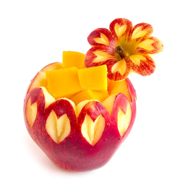 Apple red carved inside with mango cube style fruit Premium Photo