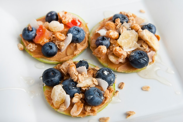 Apple slices with peanut butter and blueberries. health food. Premium Photo