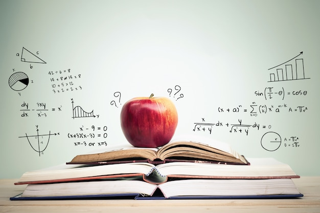 Apple on stack of open books with education doodles of books on calculus