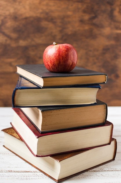 Apple on top of a pile of books front view Free Photo