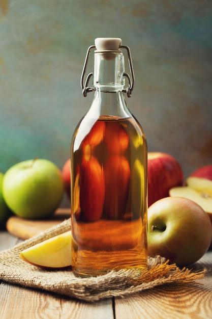 Apple vinegar. bottle of apple organic vinegar or cider on wooden background. healthy organic food. Premium Photo