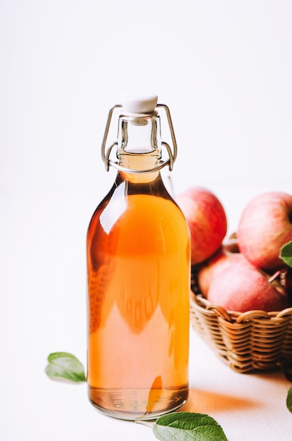 Apple vinegar in a bottle on white wooden table with apples in a basket. Premium Photo