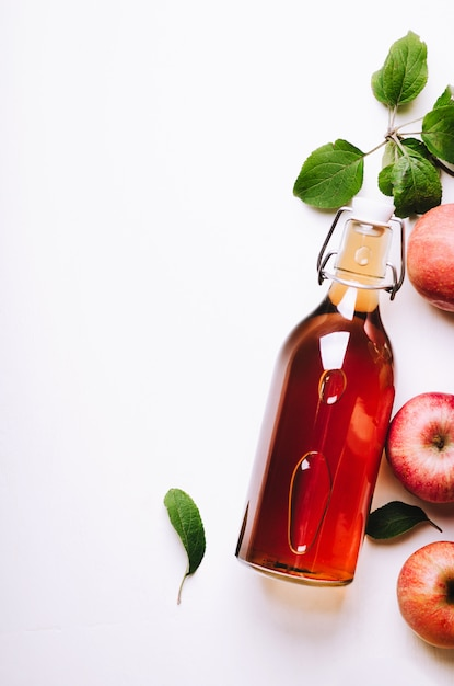 Apple vinegar in bottle on white wooden table with apples and leaves. Premium Photo