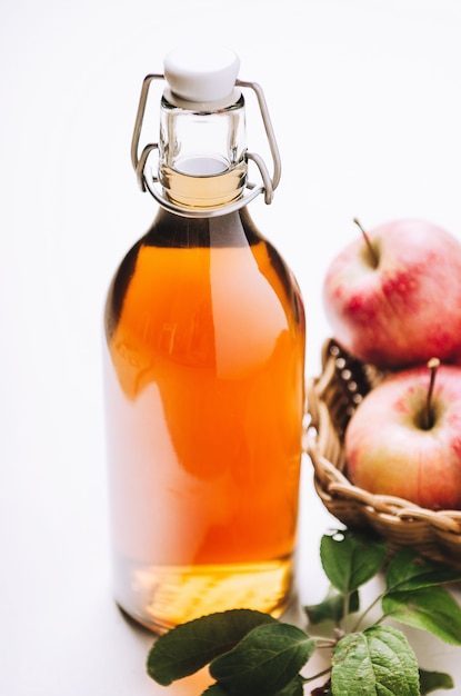 Apple vinegar in a bottle on white wooden table with apples. rustic style. Premium Photo