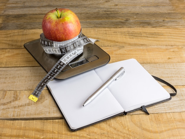 Apple over weight scale, measuring tape and notebook on wooden table Premium Photo
