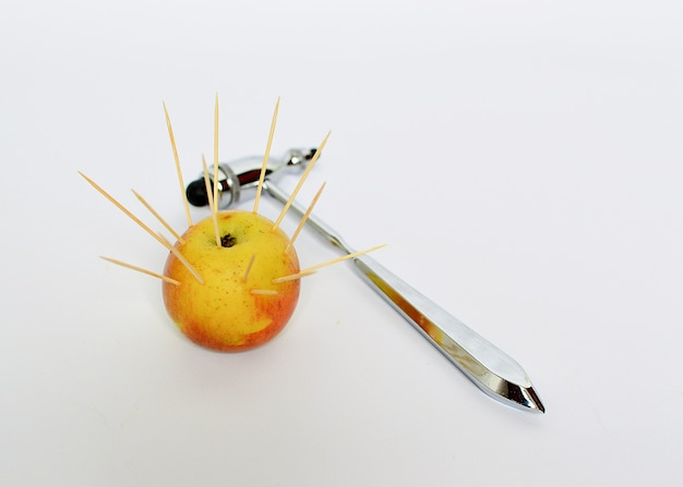 An apple in which sharp toothpicks stick out and a neurological hammer on a white background. Premium Photo