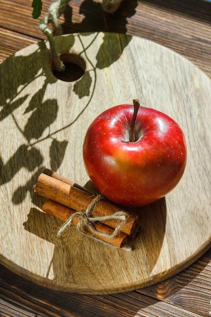 リンゴの葉、シナモンスティック、木製のまな板 無料写真
