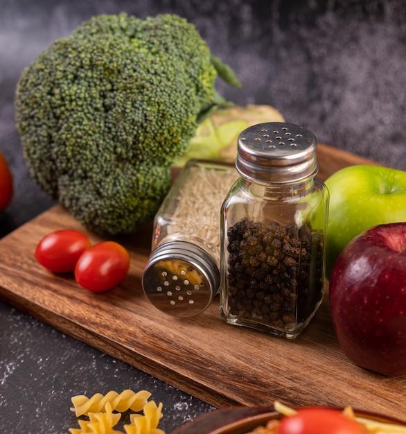Mela su una tavola di legno con un barattolo di semi di pepe Foto Gratuite