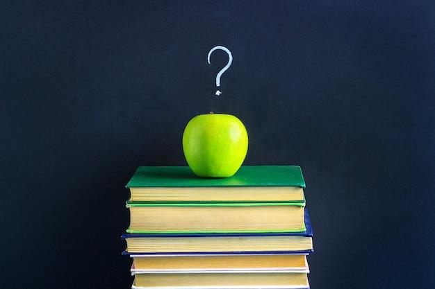 Apple на стопку книг и вопросительный знак. Premium Фотографии