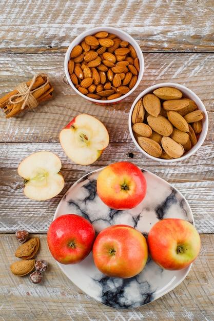 Яблоки и ломтики в тарелке с палочками корицы, очищенного и неочищенного миндаля в мисках, орехи сверху на деревянном Бесплатные Фотографии