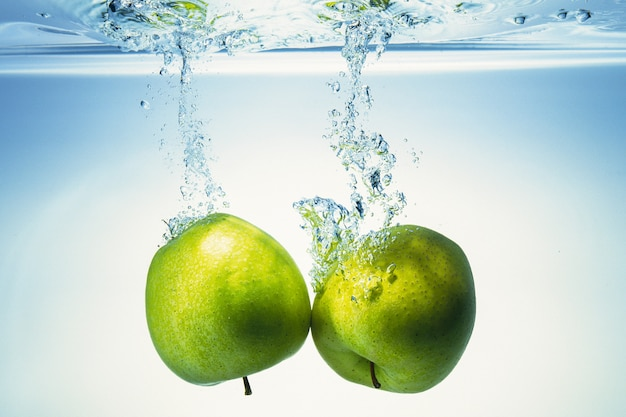 Apples are getting into the water. Premium Photo