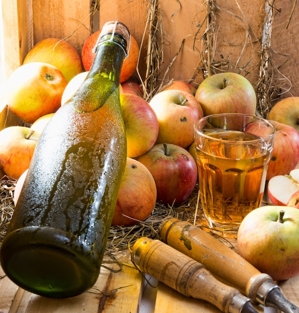Apples and a bottle and glass of cider Premium Photo