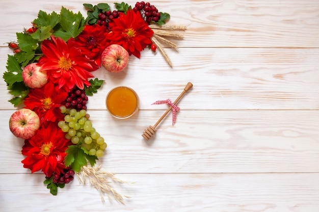 Apples, grapes, red dahlia flowers, red rowanberries and honey with copy space Premium Photo