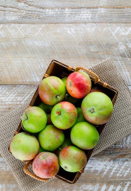 Яблоки в корзине на деревянных и салфетках, вид сверху. Бесплатные Фотографии