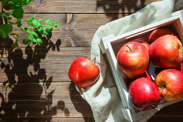 植物の近くの箱にリンゴ 無料写真