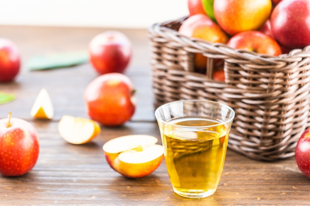 Apples juice in glass with apple in the basket Free Photo