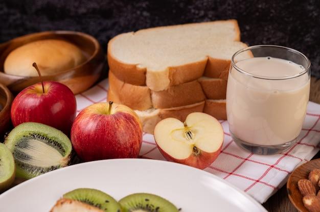 Mele, kiwi, latte e pane in un piatto su un panno bianco rosso Foto Gratuite