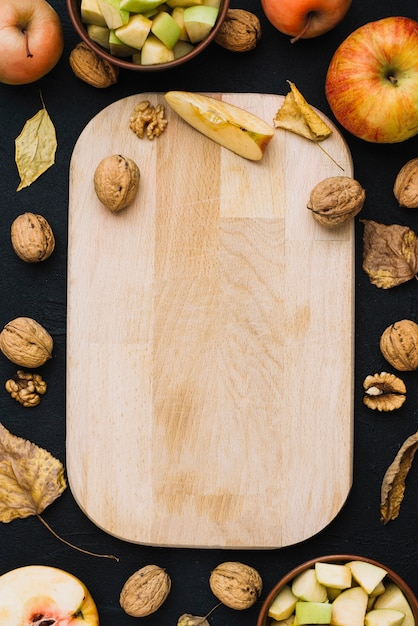 Apples and nuts around cutting board Free Photo