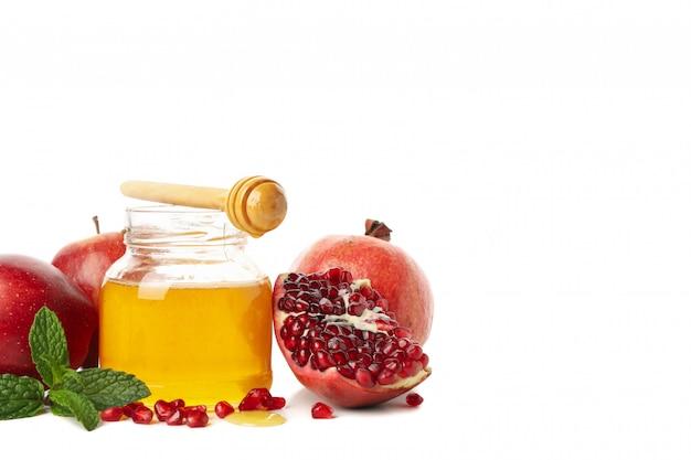 Яблоки, гранат и мед, изолированные на белом. натуральное лечение Premium Фотографии