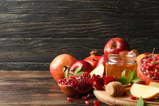 Яблоки, гранат и мед на дереве, место для текста Premium Фотографии