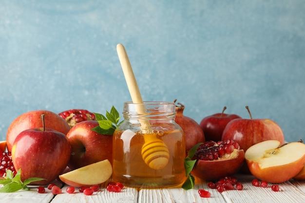 Яблоки, гранат и мед на деревянном столе, крупным планом Premium Фотографии
