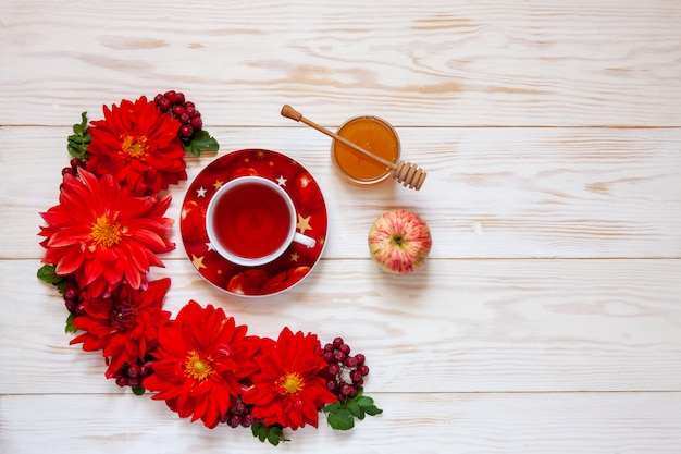 Apples, red dahlia flowers, red rowanberries and honey with copy space Premium Photo